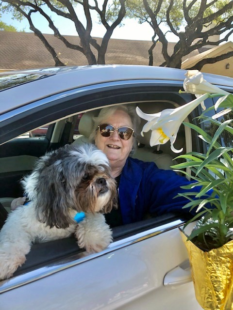 Becky Graham picking up an Easter Lily with the help of her dog.